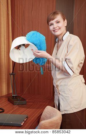 Hotel maid dusting furniture