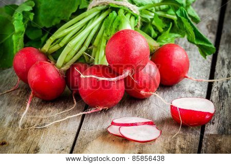 Bundle Of Bright Fresh Organic Radishes With Slices On Wooden Table