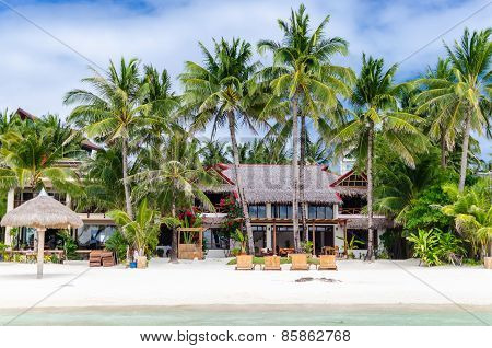 Luxury tropical villa near the sea with beautiful colourful decor surrounding palm trees and lounges in front of it at famous exotic white sandy beach on Boracay island station 1 Philippines poster