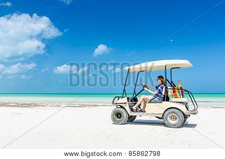 Young Woman Driving Golf Cart Along Tropical Sandy Beach During Her Caribbean Vacation
