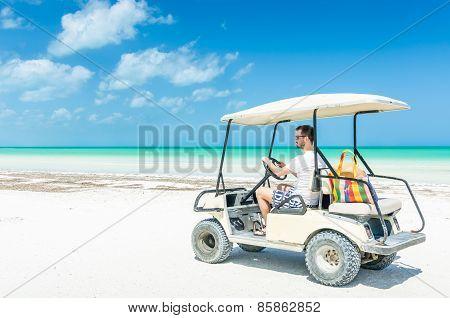 Young Man Driving Golf Cart Along Tropical Sandy Beach During His Caribbean Vacation