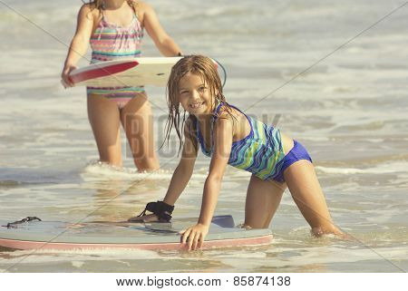 Cute Girl Playing in the Ocean on a boogie board
