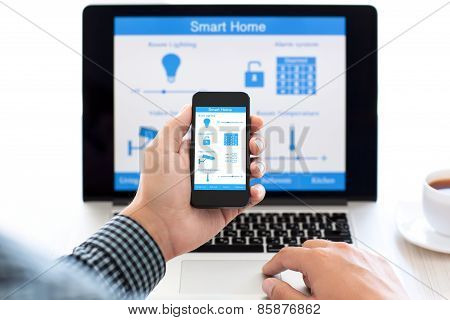 Man Holding Phone With Program Smart Home On The Screen