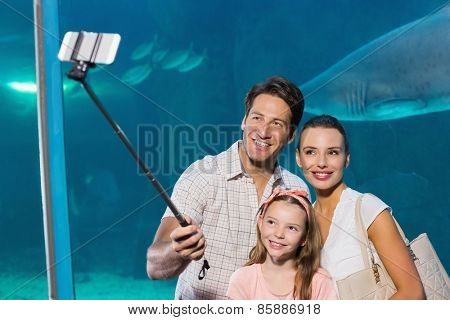 Happy family using selfie stick at the aquarium
