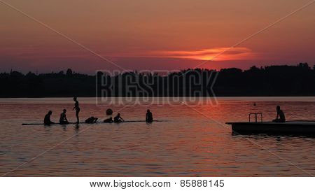 People Swimming At Sunset