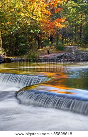 The vibrant colors of autumn foliage are reflected on the waters of Upper Peninsula Michigan's Bond Falls. poster