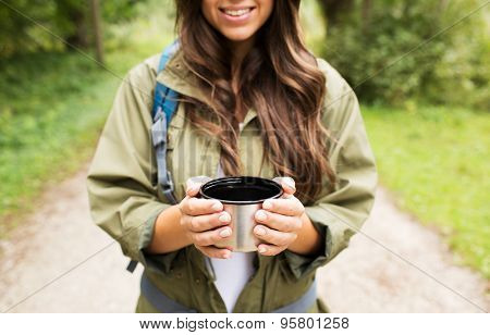 adventure, travel, tourism, hike and people concept - smiling young woman hiker with cup and backpack in forest poster