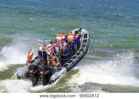 USTKA - JULY 07: Tourists enjoy a high speed boat ride on the Baltic sea near the harbour on 7 July 2015 in Ustka, Poland.