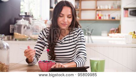 Young Woman Eating Breakfast Whilst Using Digital Tablet