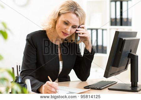 Middle-age business woman talking on the mobile phone in office. Portrait of smiling business woman.