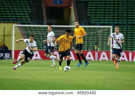 May 27, 2015 - Shah Alam, Malaysia: Malaysia's Joseph Kalang (17) dribbles the ball past Tottenham Hotspur's defenders in a friendly match in Malaysia. Tottenham Hotspur is on a Asia-Australia tour.