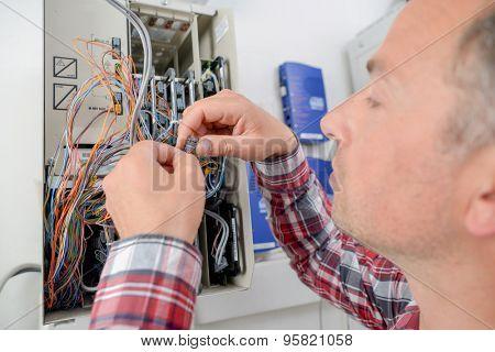 Electrician repairing a fusebox poster
