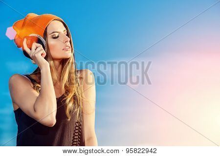 Modern young woman listening to music on headphones outdoor. Trendy teenager girt over blue sky background. Youth style.  poster