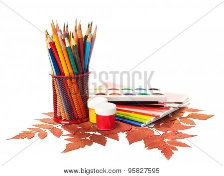 School equipment with pencils, paints , brushes and  autumn leaves  isolated on white.  Back to school concept. School stationery