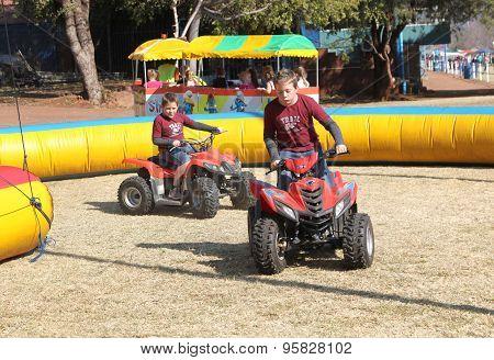 Boys Riding On Quad Bikes At Festival