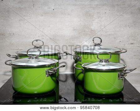 Four green enamel stewpots on black induction cooker