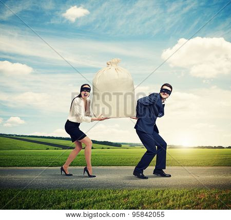happy couple of thieves carrying bag and running on the road