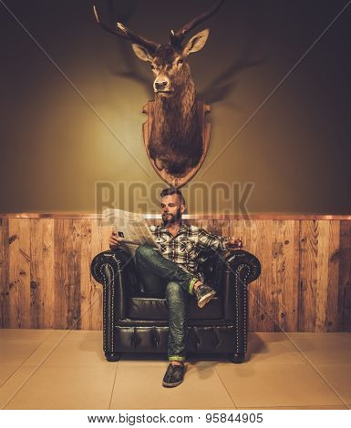 Middle-aged hipster reading newspaper on leather chair will glass of whiskey