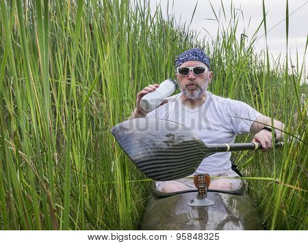 tired senior male paddler takes break from paddling a kayak and hydrating deep inside  reeds