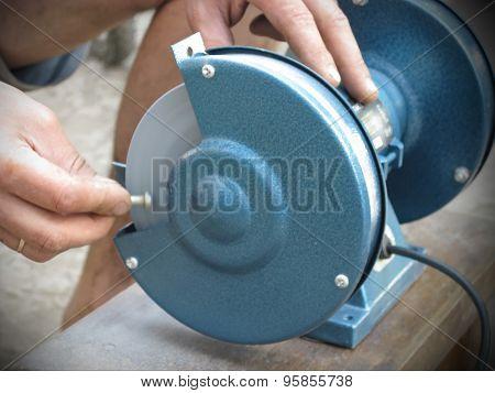 man grinds smooth a screw-bolt
