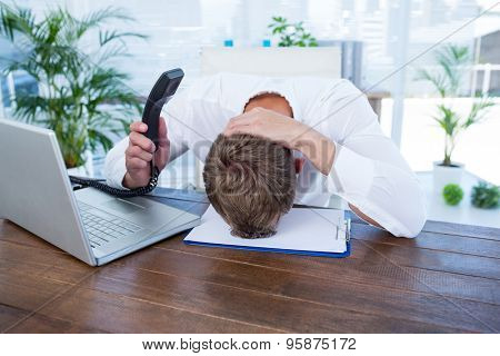 Irritated businessman holding a land line phone in the office