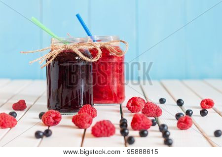 Rustic Mason Jars with raspberry jam and bog bilberry marmalade, fresh berries on white wooden backg