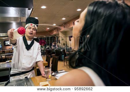 Japanese Chef Squirting Sake Drink Into Woman's Mouth At Restaurant