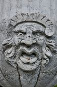 Ugly face sculpture grimacing on stone wall poster