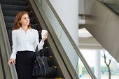 Dreamy businesswoman going down the escalator in office building poster