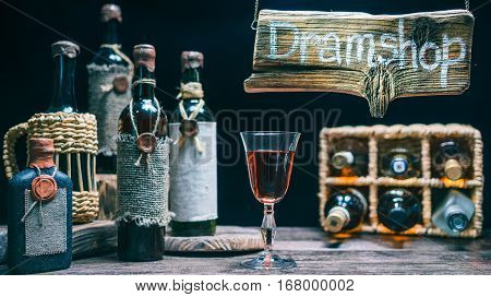 Hanging sign above dram shop counter. Vintage wine bottles on the counter and wicker basket. Concept for online or offline dram store