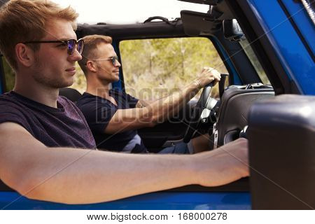 Two Male Friends Driving Open Top Car On Country Road