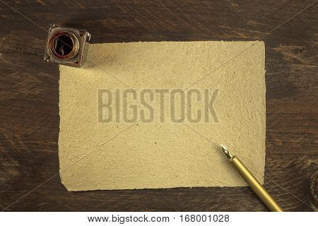 An overhead photo of a blank piece of old paper on a dark wooden background texture with a golden ink pen and ink bottle. A mockup or a banner with copy space