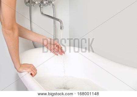Woman running a bath with warm water and bubbles, closeup