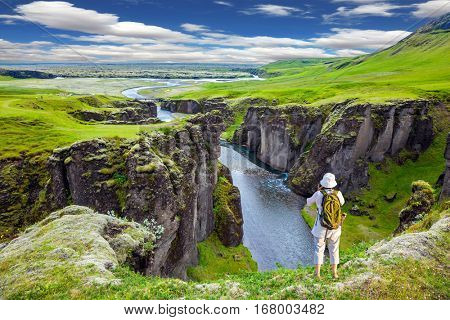 The striking canyon Fyadrarglyufur in Iceland. Green Tundra in summer. The elderly woman standing on a rock and photographing the scenic landscape. The concept of active northern tourism