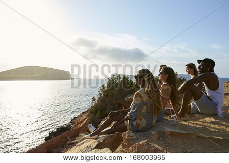 Side View Of Friends Sitting On Cliff Watching Sunset