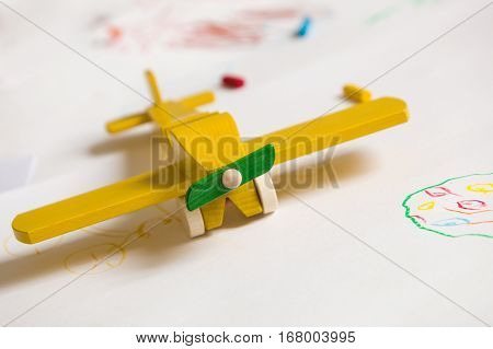 Yellow wooden toy plane on the white background. Education children play concept. Kids drawings with the toy. Childhood. Happy. Joy. Kindergarden.