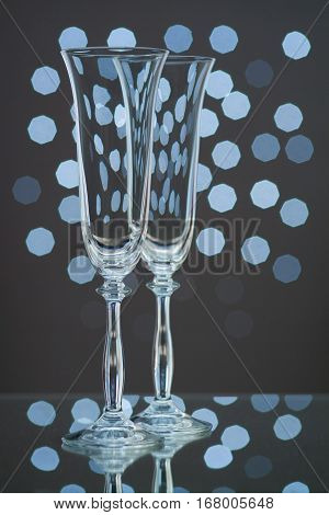 Two empty champagne glasses on blue bokeh background