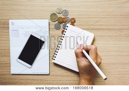 Hand Writing On Note Book With Smartphone Or Mibile Phone On Bank Book Account And Coins