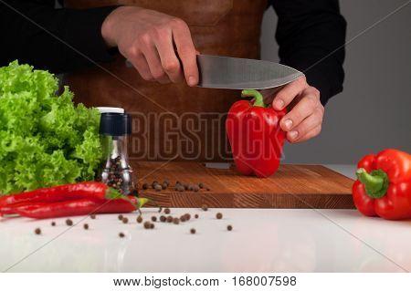 Man cutting red big peeper on the wooden cutting board