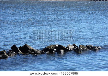 sharp river rocks in front blue river behind