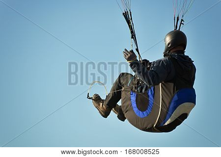 One paragliding in a beautiful blue sky