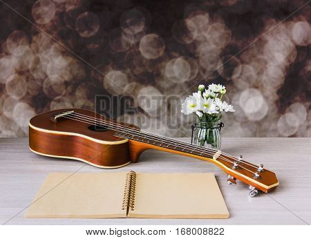 Ukulele And Blank Note Book With Pencil And Flower On Dark Bokeh Background