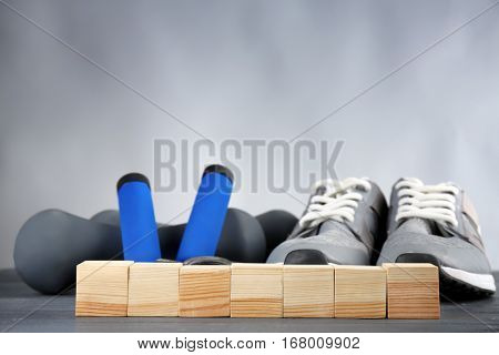 Cubes with space for text, jogging shoes and dumb-bells on grey background
