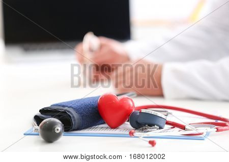 Sphygmomanometer, red heart and stethoscope on doctor table, close up view