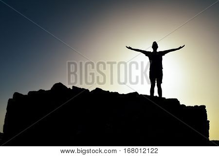 the silhouette of a young caucasian man with open arms in the air, on a monticule, backlighted by the sun at his back