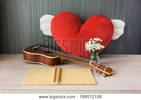 Ukulele And Big Fly Red Heart With Blank Note Book With Pencil And Flower For Love Music Concept
