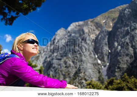 Young woman hiker resting and relaxing in beautiful inspirational Greek mountains landscape. Hiking trip in Samaria Gorge Canyon Crete. Young girl backpacker resting and camping outdoors in nature.