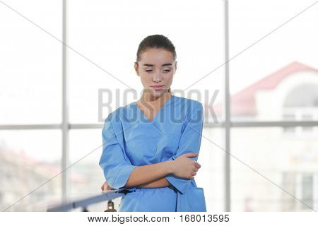 Depressed medical worker standing near banisters in clinic