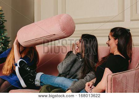 Three beautiful young girls throw pillows. Studio horizontal close-up portrait