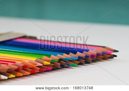 Multicolored pensils in the box on the white paper. Back to school. Copy space. Top view.